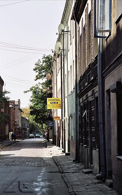 """Ulica Warszawska widziana od strony ulicy Legionów.<br>W tle widoczny szyld """"wiecznego"""" sklepu """"Iskra"""", w którym w latach osiemdziesiątych przychodziliśmy ze szkoły pooglądać zabawki a nasze mamy kupowały nam zeszyty."""