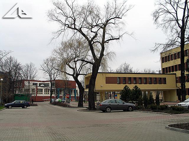 Plac parkingowy otoczony budynkami Urzędu Miejskiego, Powiatu Wołomińskiego oraz Sądu Rejonowego.